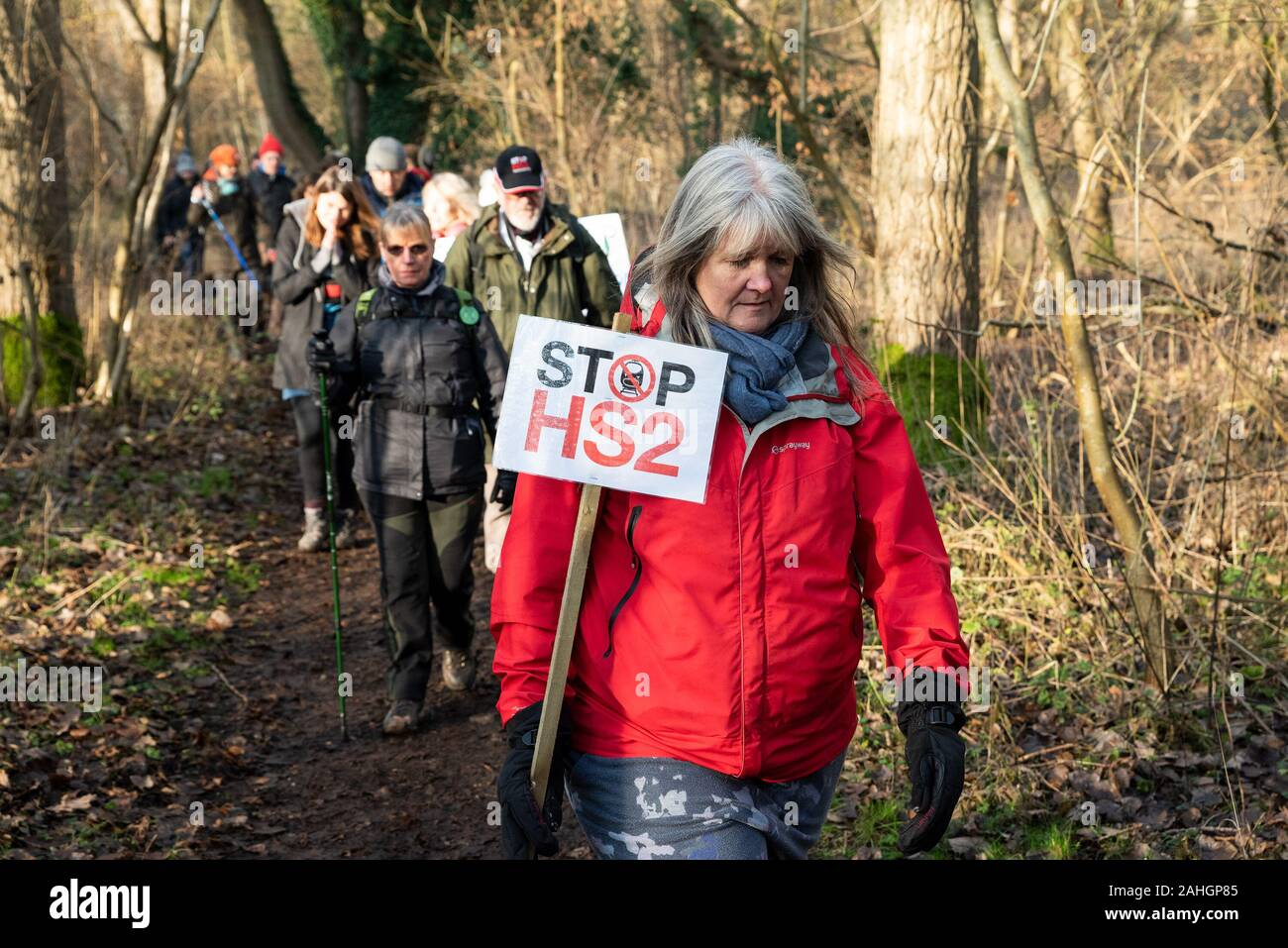 Denham, UK. 29th December 2019. Stand for the Trees, a Walk for Wildlife and Water, organised by Chris Packham and supported by Extinction Rebellion, #ReThinkHS2, Save the Colne Valley, STOP HS2 and Hillingdon Green Party. Speakers described the threats to the habitats that are the homes of endangered eels, bats, otters, water voles, the loss of 28,000 trees to HS2 and the chalk aquifer that contributes to much of London's water. Pictured, woman in red jacket holding Stop HS2 placard while walking though woodland. Credit: Stephen Bell/Alamy Stock Photo