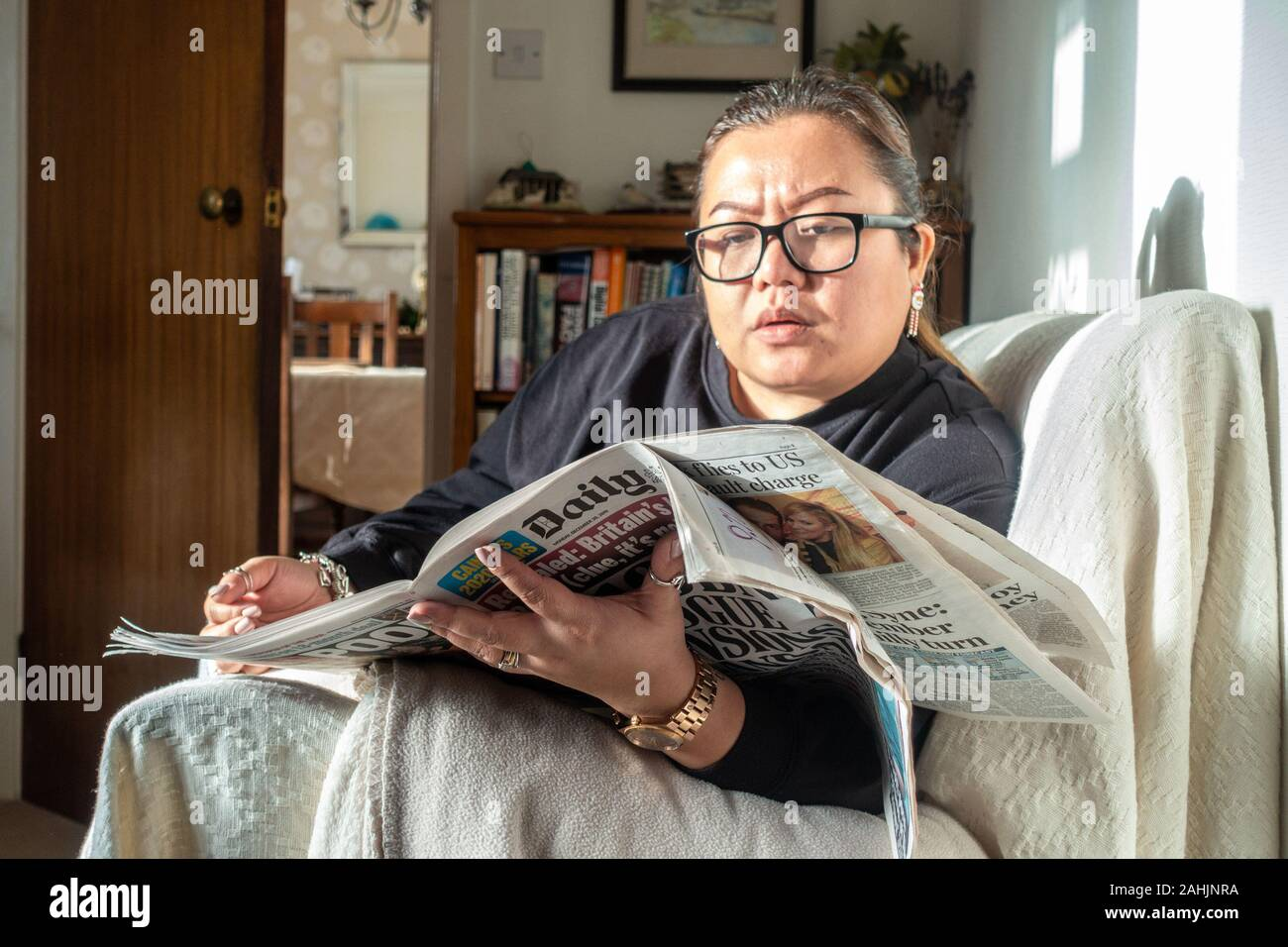 a-lady-sits-on-a-settee-and-reads-a-newspaper-2AHJNRA.jpg