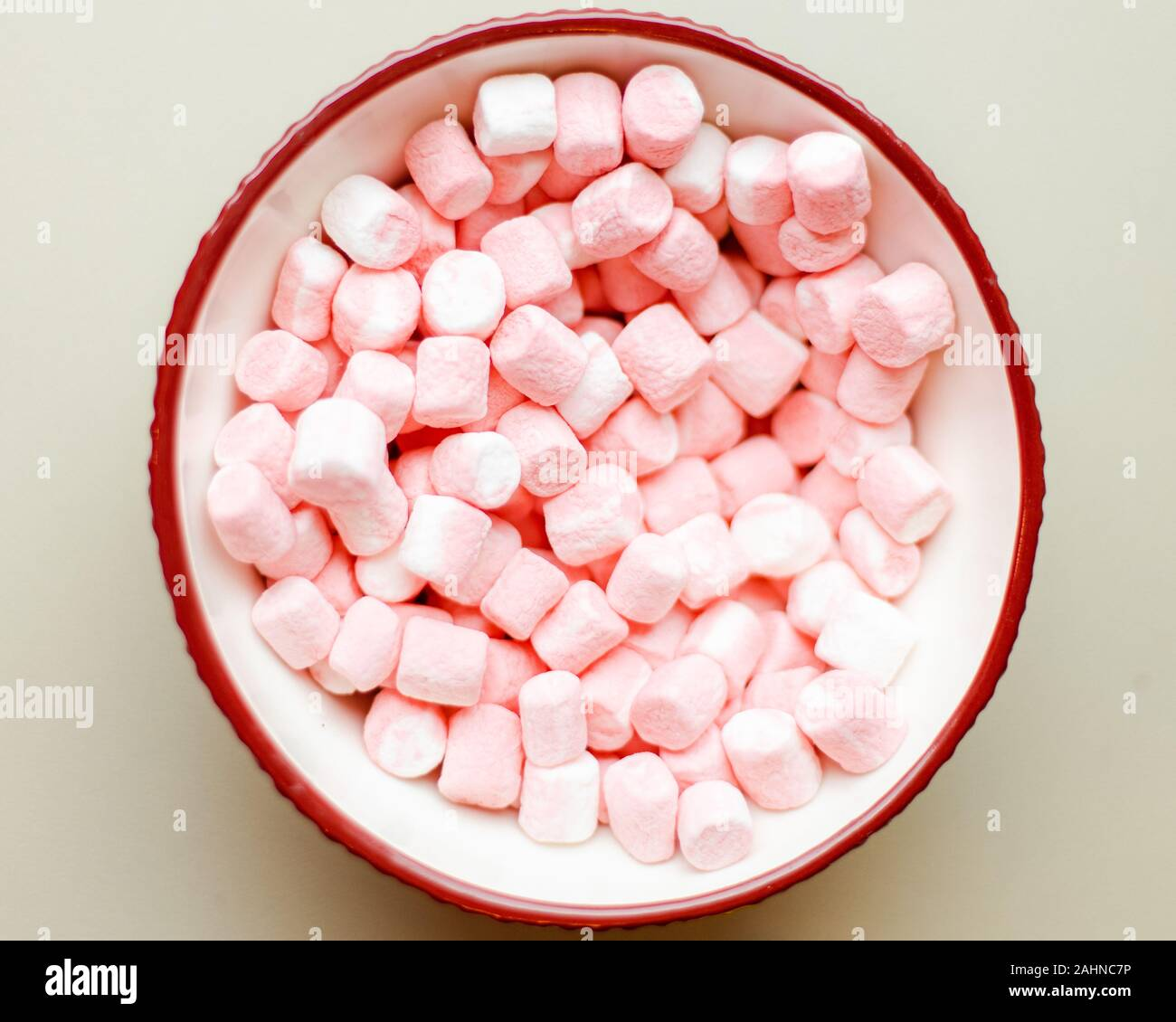 small miniature tasty sweet sugary pink and white marshmallows in holiday bowl top down shot Stock Photo