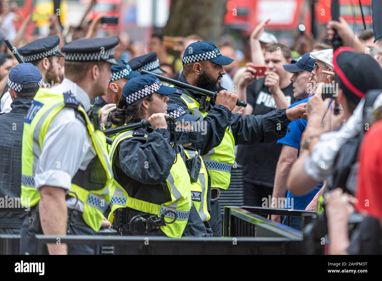 police-officers-including-a-male-officer-with-muslim-features-defending-downing-street-whitehall-london-uk-with-batons-raised-during-brexit-rally-2AHPM3T.jpg