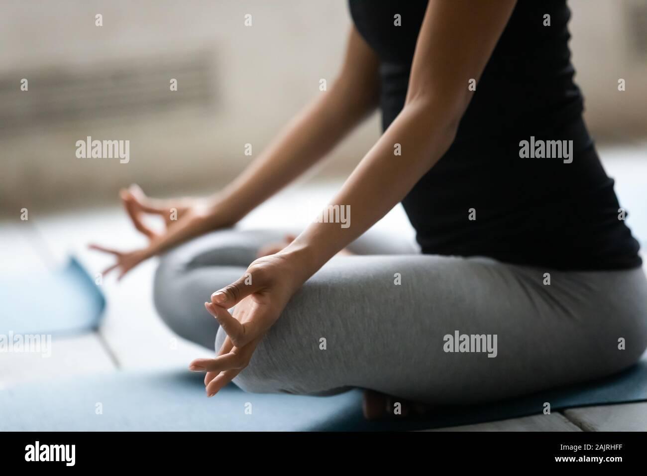 Close up African American woman doing Padmasana exercise, practicing yoga Stock Photo