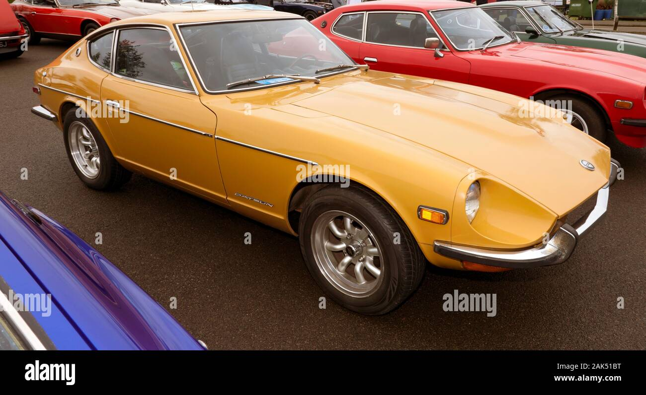 Three-quarter front view of a 1971, Orange, Datsun 240Z,  on display in the Car Club Zone of the 2019 Silverstone Classic Stock Photo