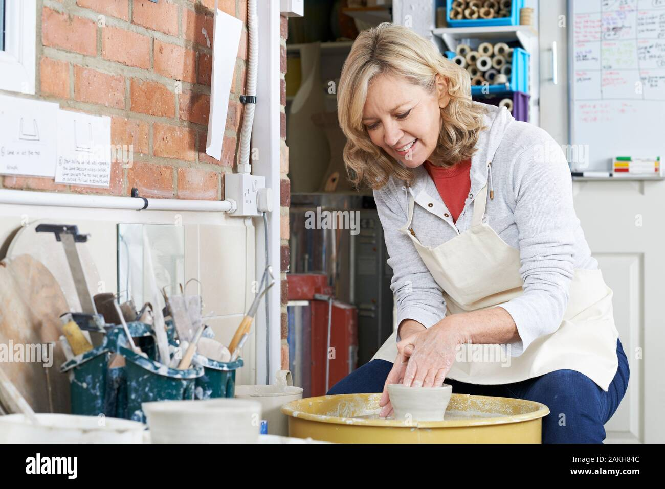 Mature Woman Working At Potters Wheel In Studio Stock Photo