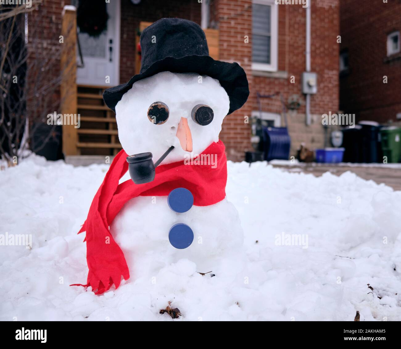 snowman-dressed-with-red-scarf-black-felt-hat-blue-buttons-smoking-a-pipe-in-front-of-leaside-residence-2AKHAM5.jpg