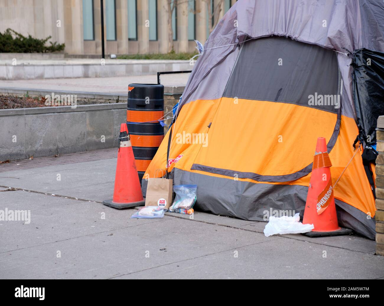 food-donations-at-door-of-homeless-tent-set-up-on-sidewalk-on-university-avenue-in-the-centre-of-toronto-on-a-cold-grey-winter-day-2AM5W7M.jpg