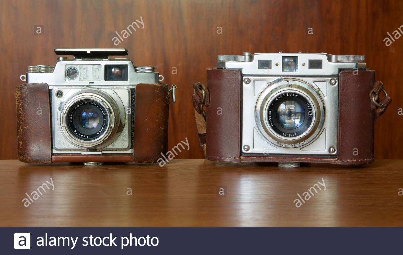 Two vintage cameras in their original leather brown casing, an Agfa Ambi Silette and a Braun Nurnberg Gloria Stock Photo