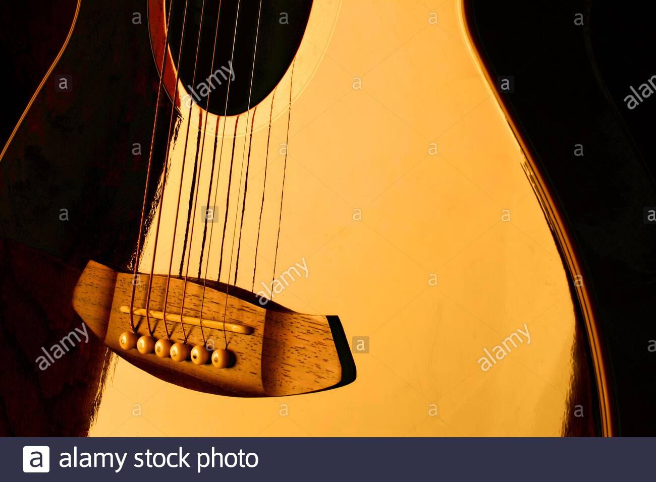 close-up-of-an-electro-acoustic-guitar-reflecting-golden-light-2AP4TDP.jpg