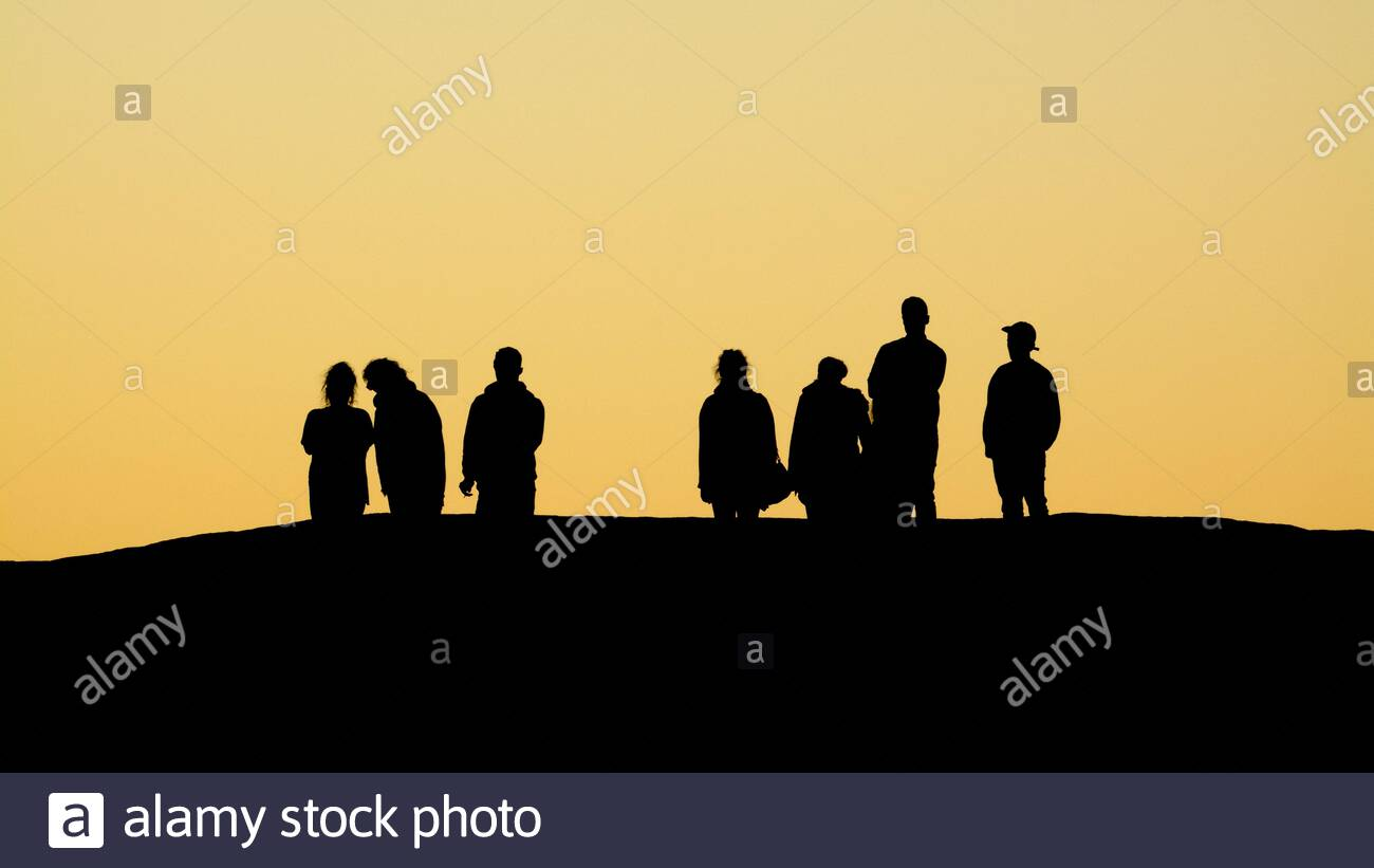 seven-young-people-in-silhouette-watching-the-sunset-from-a-high-rock-2AP4WAG.jpg