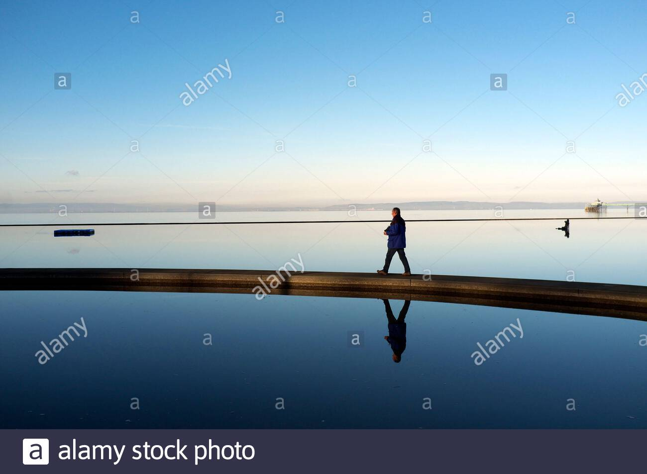 A man walks along a walkway across the Marine Lake on Clevedon seafront during a calm winter's day. Clevedon, North Somerset, UK. Stock Photo