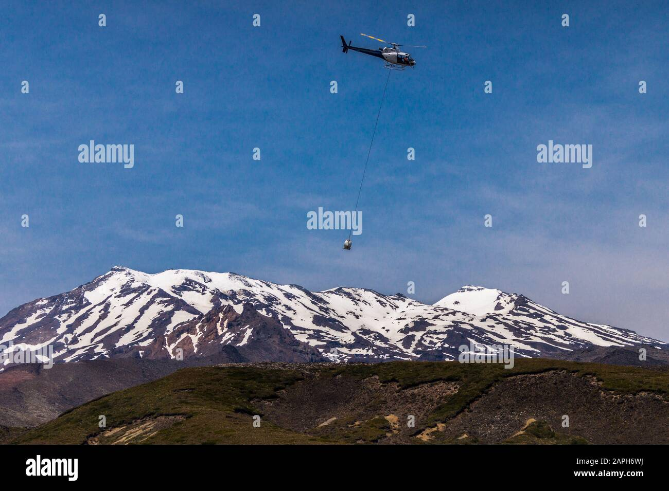 helicopter-on-public-toilet-cleaning-duty-flying-past-mount-ruapehu-tongariro-national-park-north-island-new-zealand-2APH6WJ.jpg