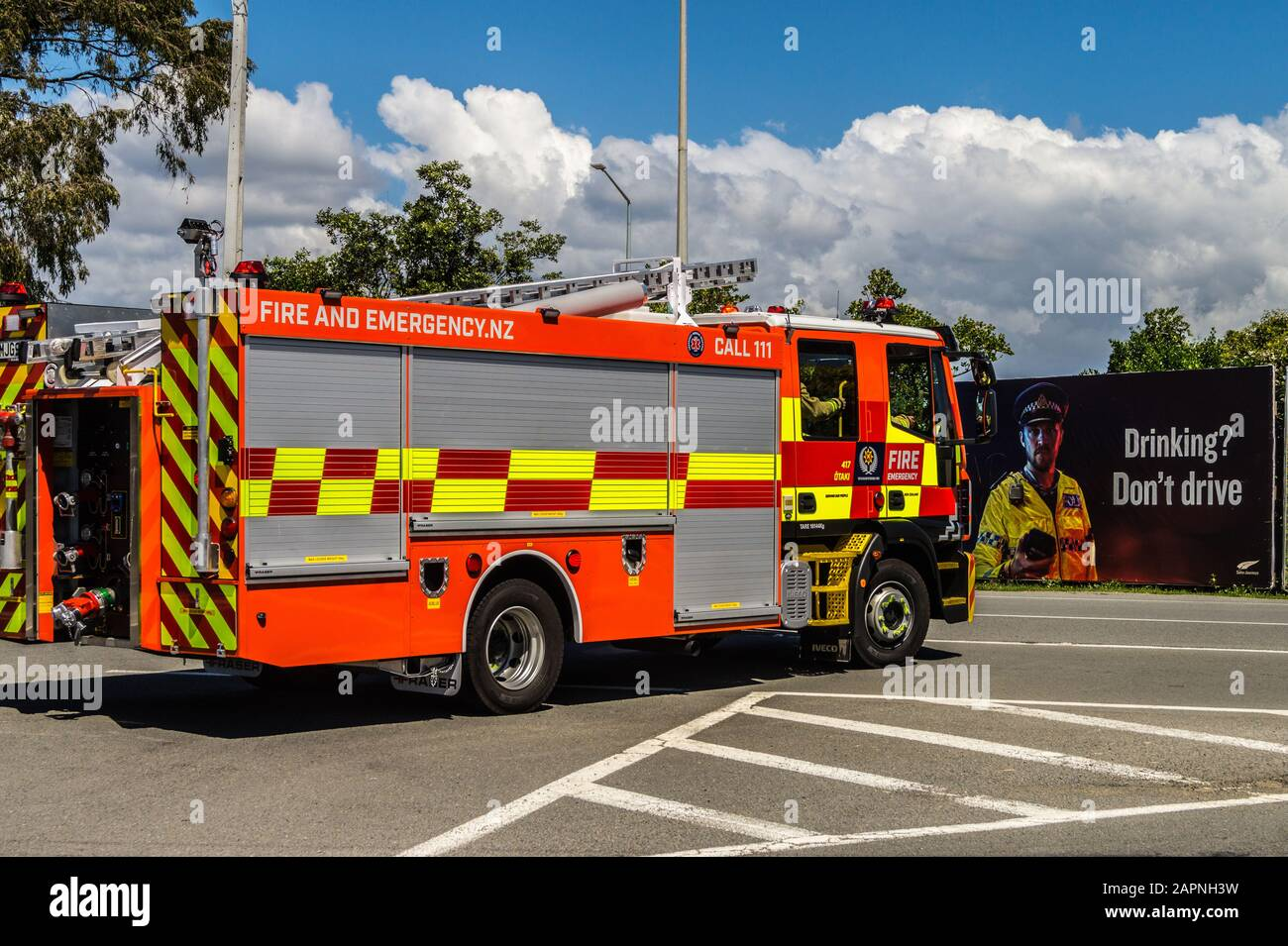 iveco-ec1225-fire-appliance-responding-to-an-emergency-call-passing-a-drink-driving-poster-taki-north-island-new-zealand-2APNH3W.jpg