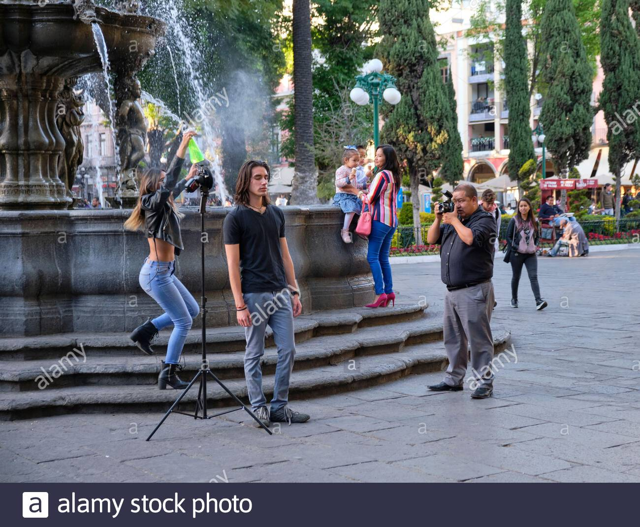 male-model-posing-for-photo-shoot-in-central-zocalo-while-female-assistant-sprays-a-water-mist-bottle-group-is-standing-by-a-fountain-in-puebla-2ARBMGX.jpg