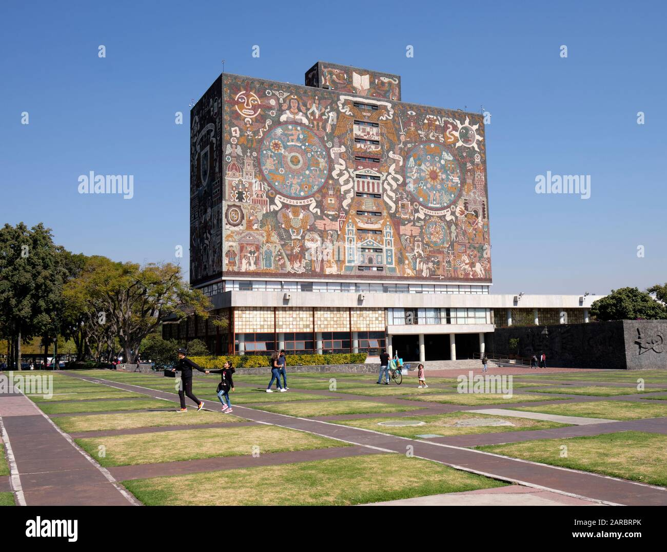 Mexico city University campus library iconic facade  created by the Mexican artist Juan O'Gorman with people walking by Stock Photo