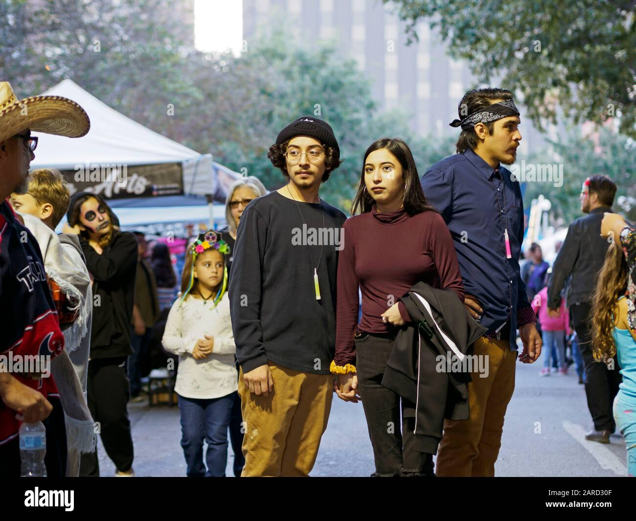 a-young-couple-holds-hands-in-downtown-corpus-christi-texas-usa-during-the-2019-dia-de-los-muertos-celebration-2ARD30F.jpg