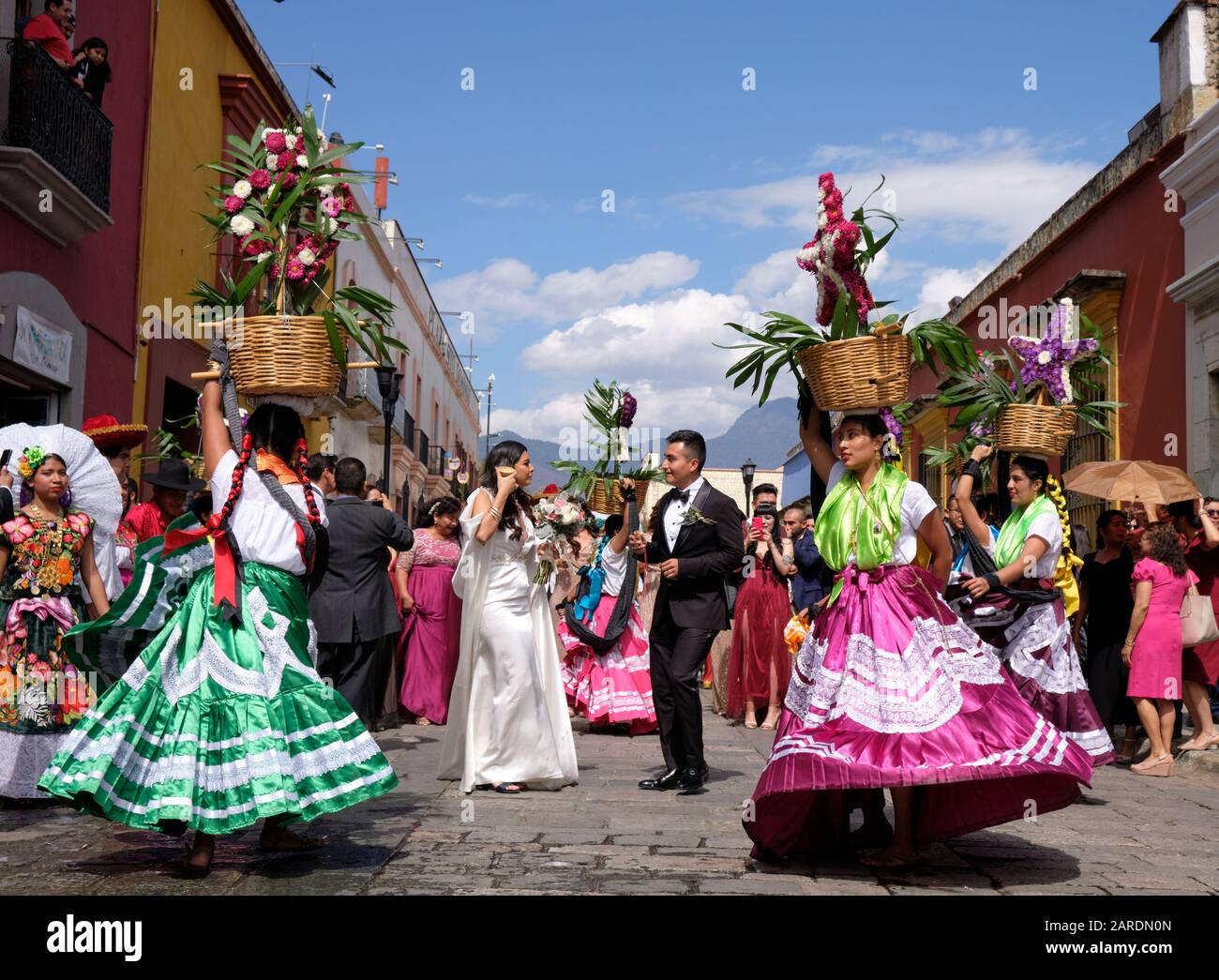 bride-and-groom-framed-by-woman-in-traditional-outfit-part-of-traditional-wedding-parade-calenda-de-bodas-on-the-streets-of-oaxaca-2ARDN0N.jpg