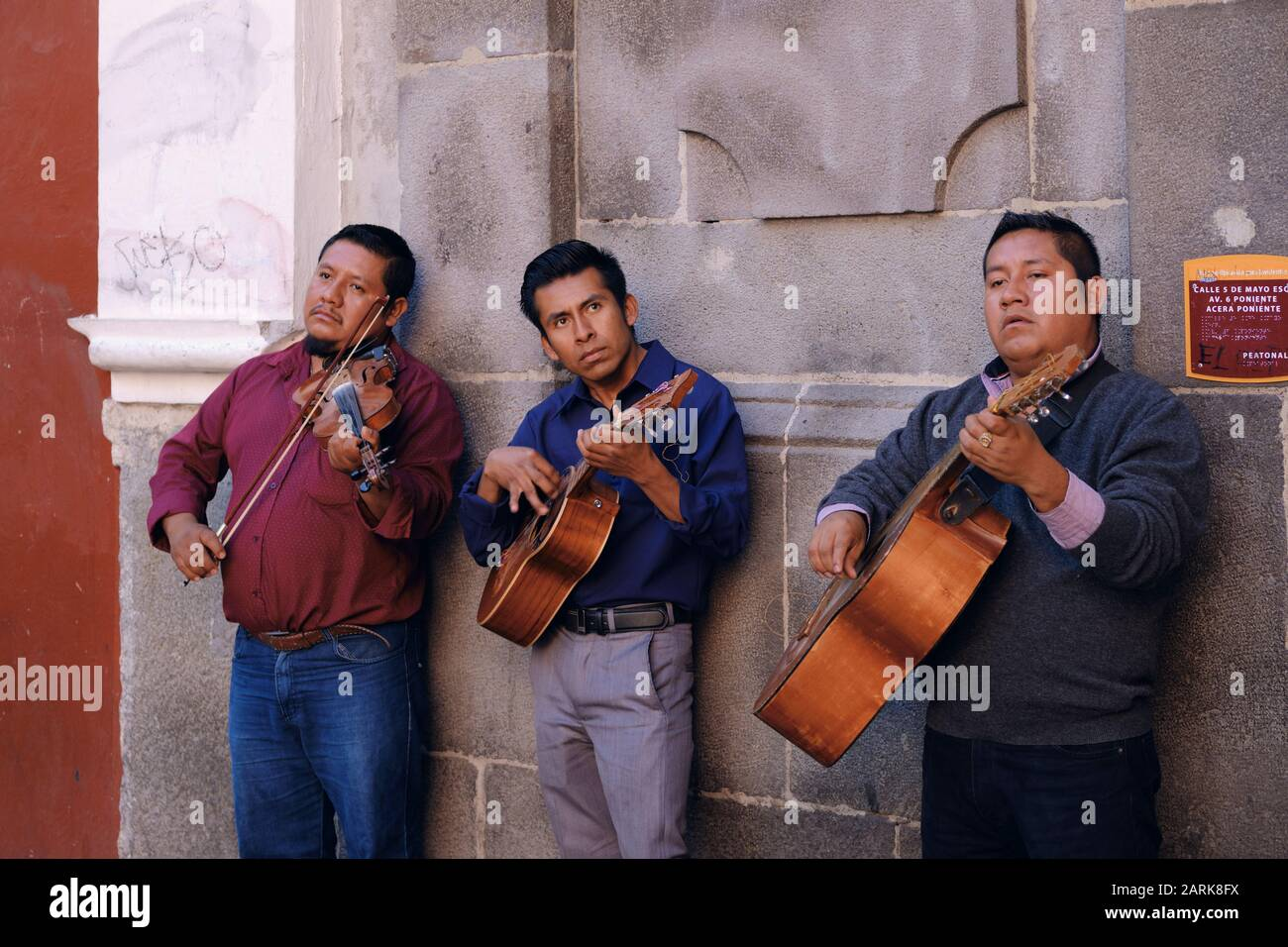 three-mexican-musicians-playing-string-instruments-against-a-wall-in-old-town-puebla-mexico-2ARK8FX.jpg