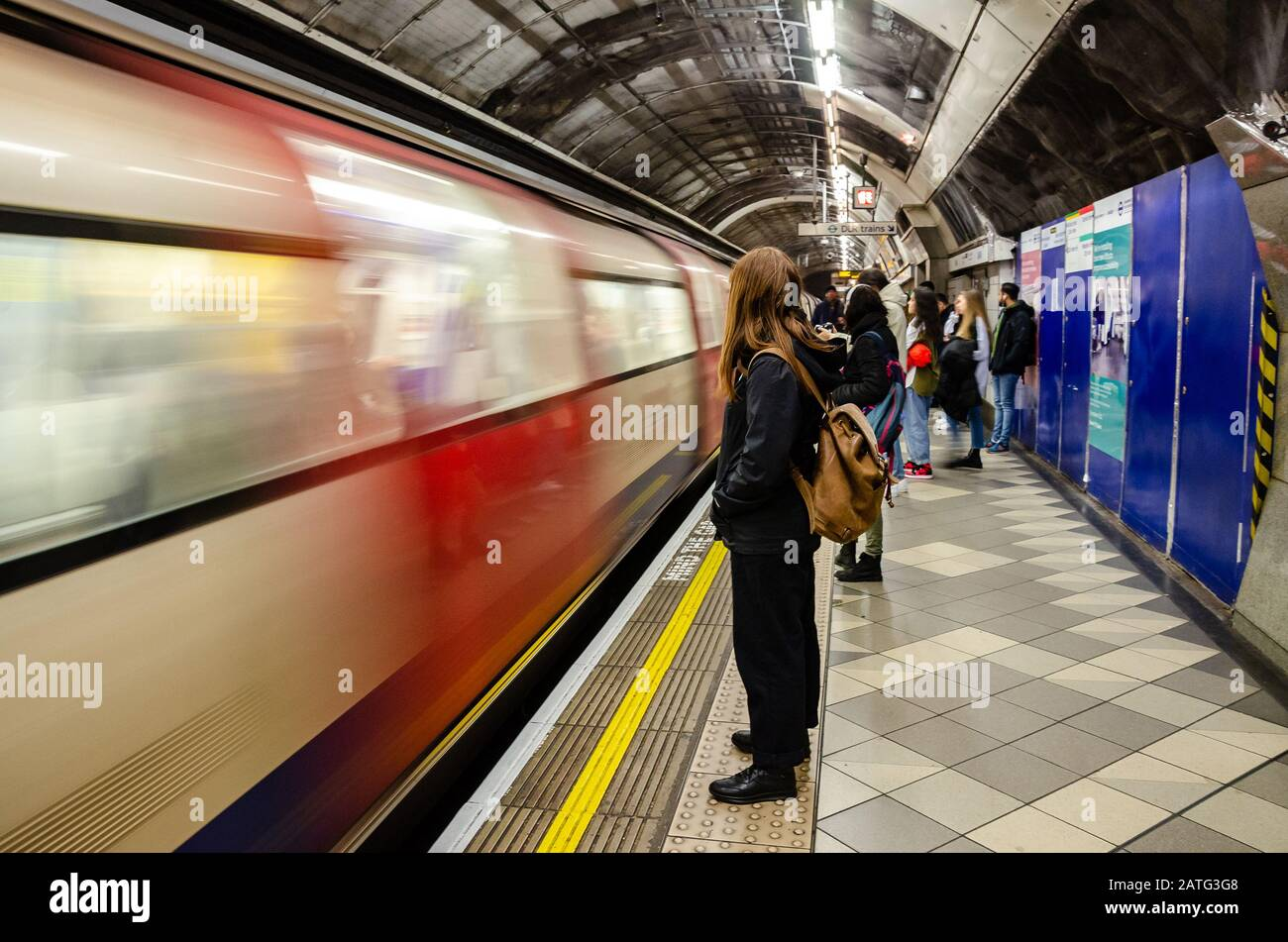 passengers-stand-and-wait-on-the-platform-as-a-london-underground-train-pulls-into-the-platform-at-bank-station-2ATG3G8.jpg