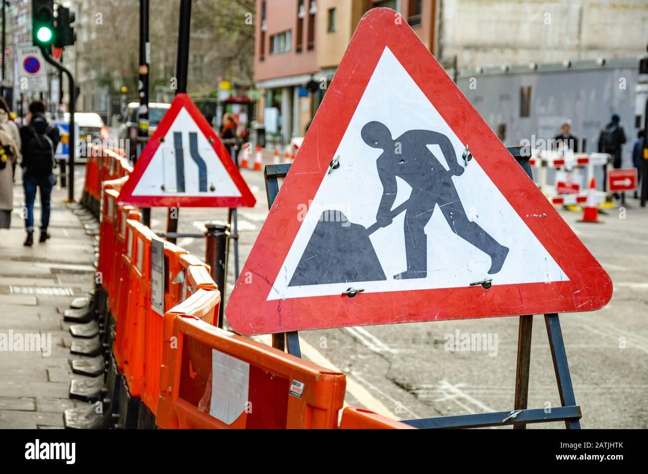 red-triangular-road-signs-warn-of-roadworks-and-narrow-lanes-2ATJHTK.jpg