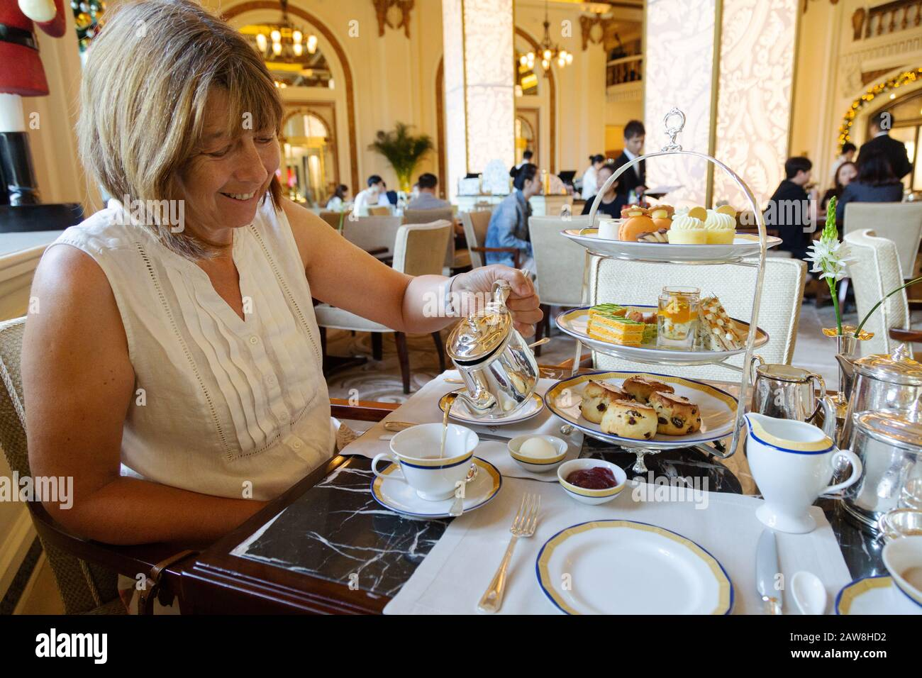 a-middle-aged-caucasian-woman-having-afternoon-tea-the-peninsula-hotel-hong-kong-asia-2AW8HD2.jpg