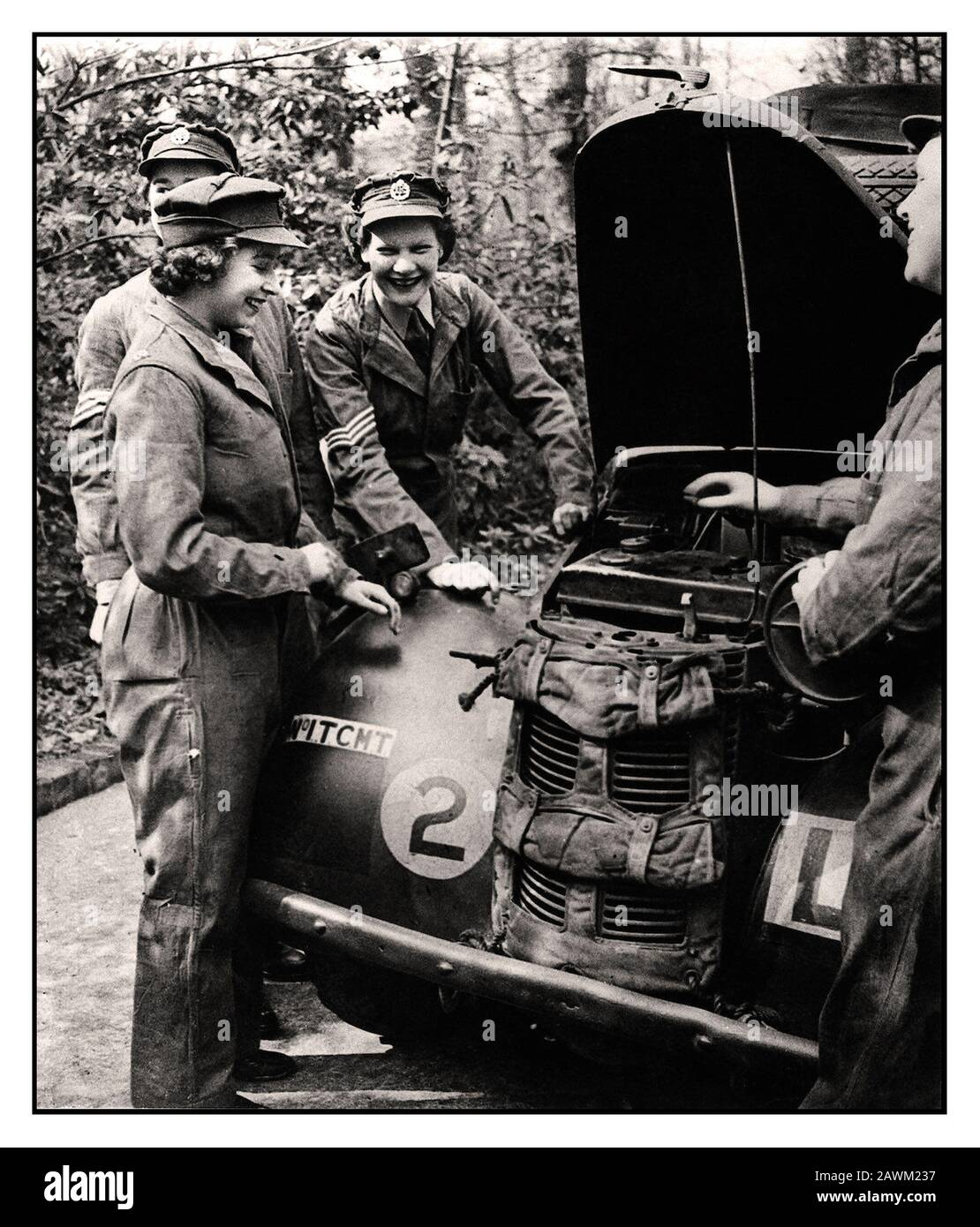 Princess Elizabeth ATS 1940's World War II Car Mechanic. HRH Princess Elizabeth (future Queen Elizabeth II) in her uniform of the ATS The Auxiliary Territorial Service a women's army auxiliary branch, with other smiling ATS service members working on and servicing a British Army military vehicle. Stock Photo