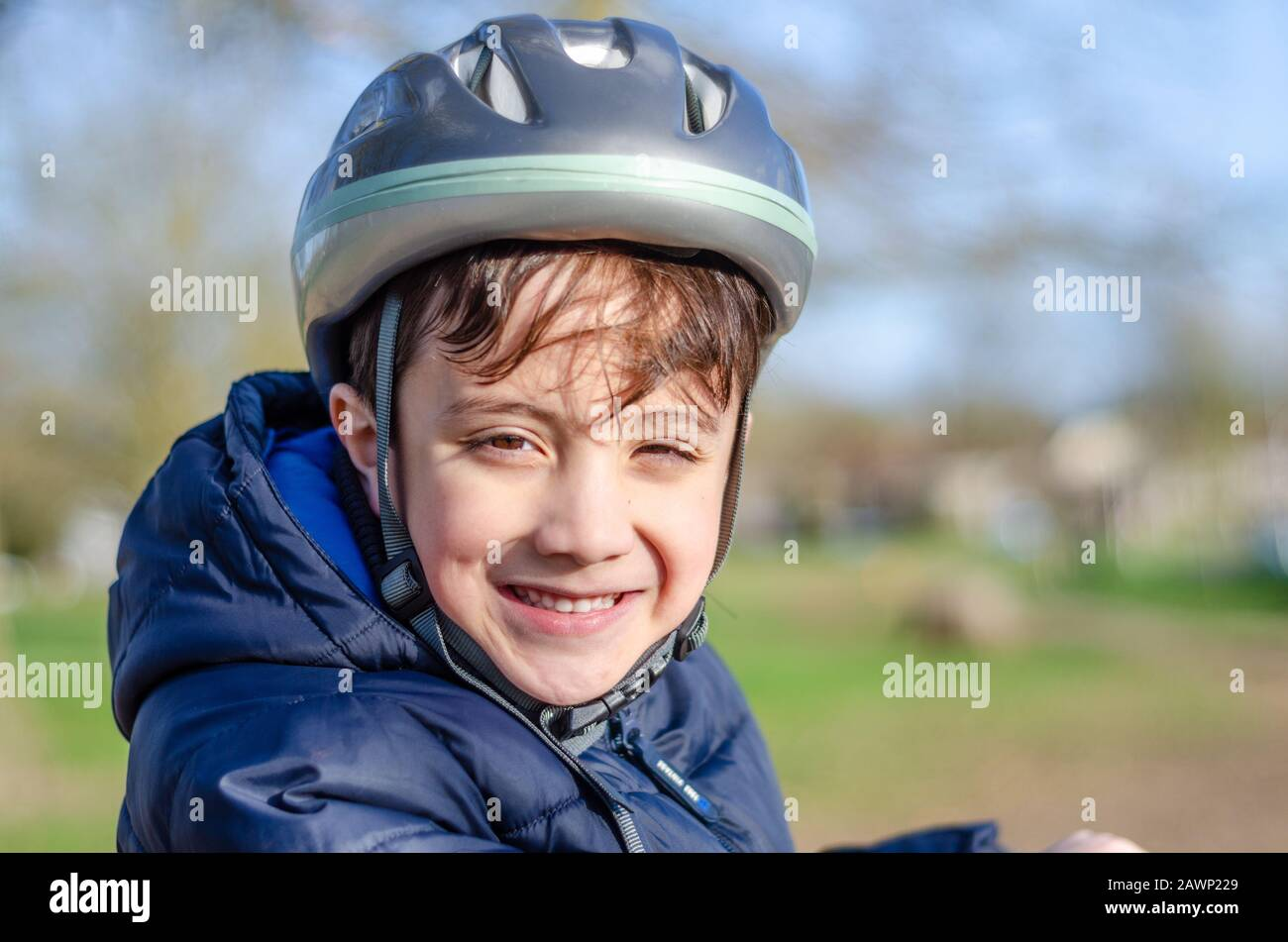 portrait-of-a-young-boy-outdoors-wearing-a-bicycle-helmet-and-smiling-2AWP229.jpg