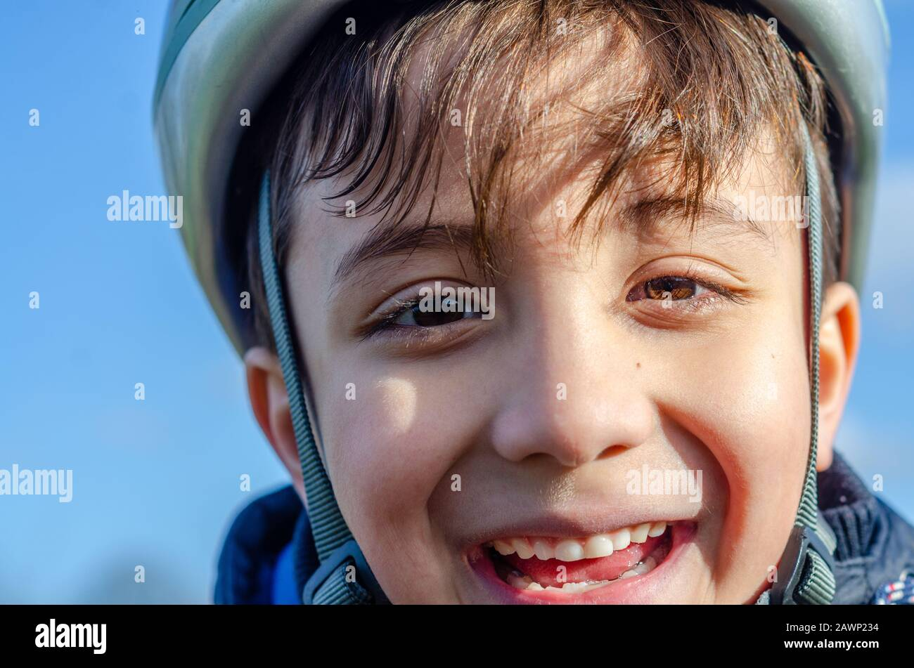 portrait-of-a-young-boy-outdoors-wearing-a-bicycle-helmet-and-smiling-2AWP234.jpg