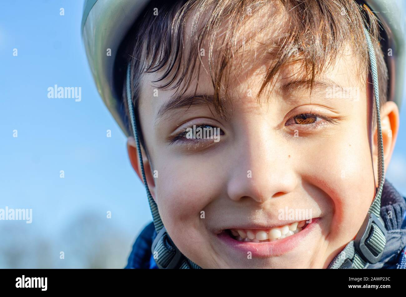 portrait-of-a-young-boy-outdoors-wearing-a-bicycle-helmet-and-smiling-2AWP23C.jpg