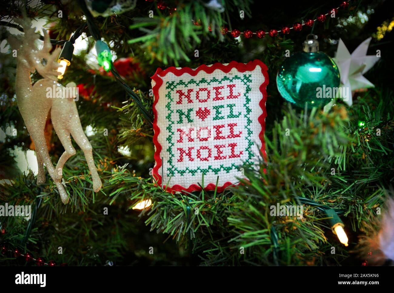 Hand stitched Christmas ornament with the word Noel embroidered on it. Handmade needlepoint Christmas decoration hanging on the tree. Stock Photo