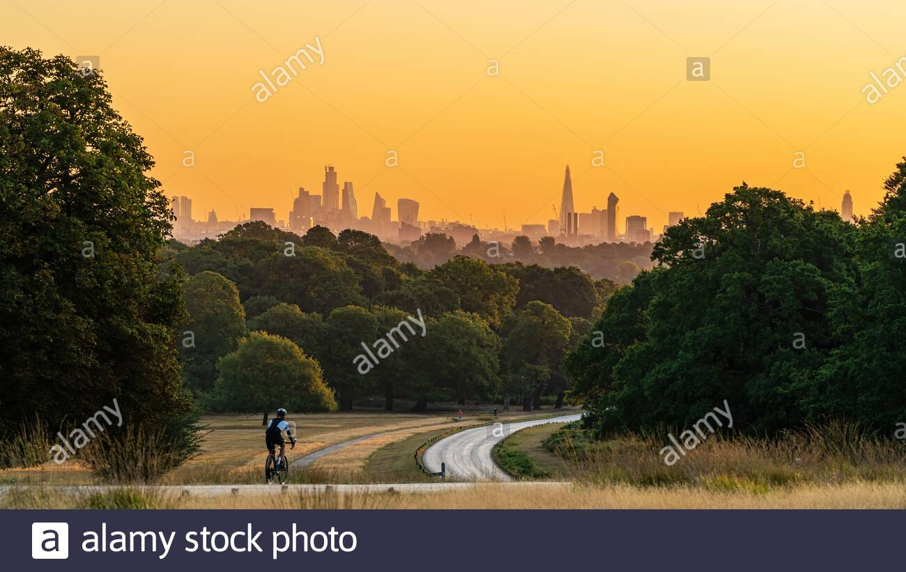 A man cycles along a road through Richmond Park towards the skyline of the City of London in the distance one early morning at dawn Stock Photo