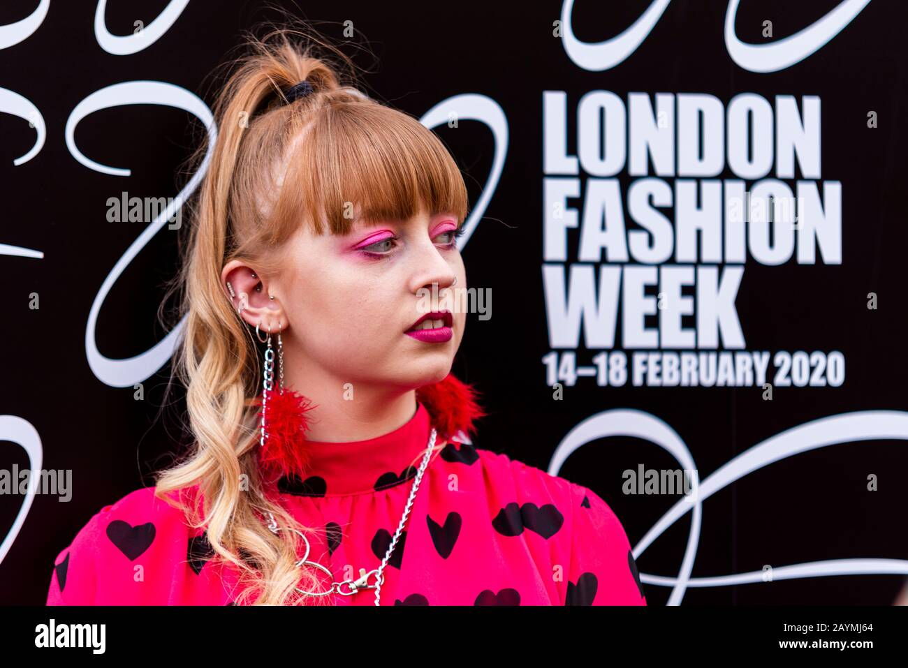 a-fashionista-female-posing-in-the-strand-outside-the-store-during-london-fashion-week-2020-brand-logo-pink-eye-shadow-dates-2AYMJ64.jpg
