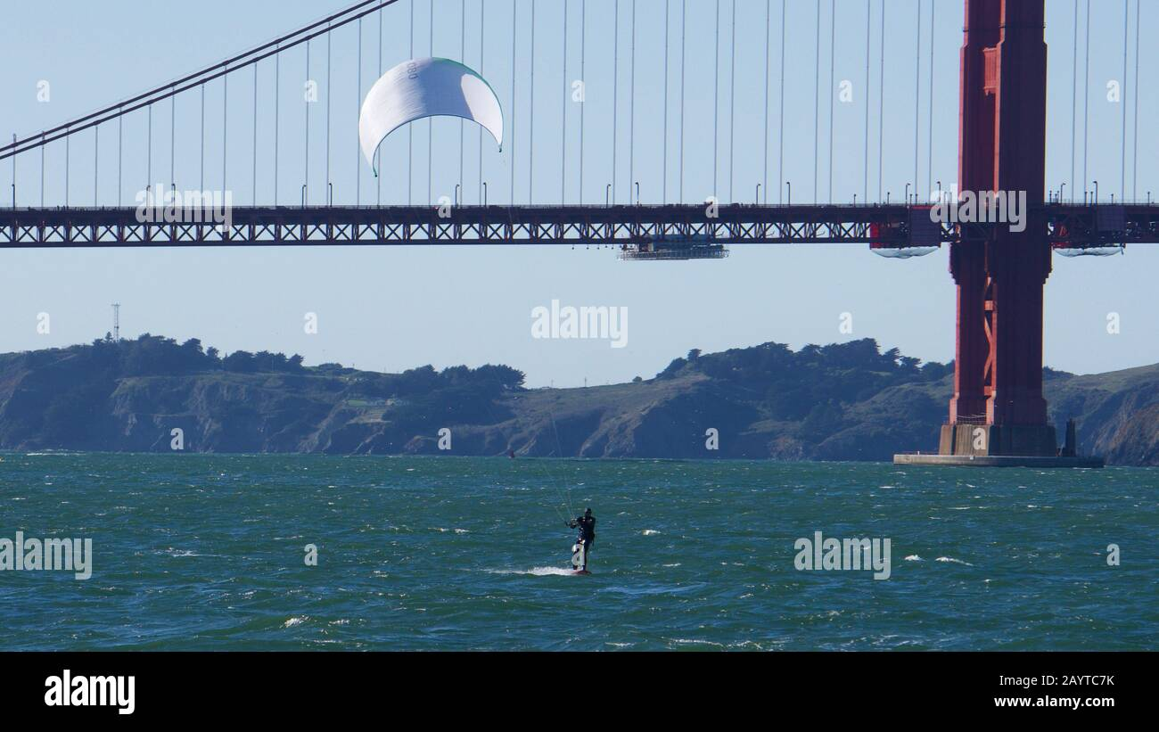 Kite surfer or kiteboarder with white sail on a windy day in front of the Golden Gate Bridge and the Marin Headlands, San Francisco Bay. Stock Photo