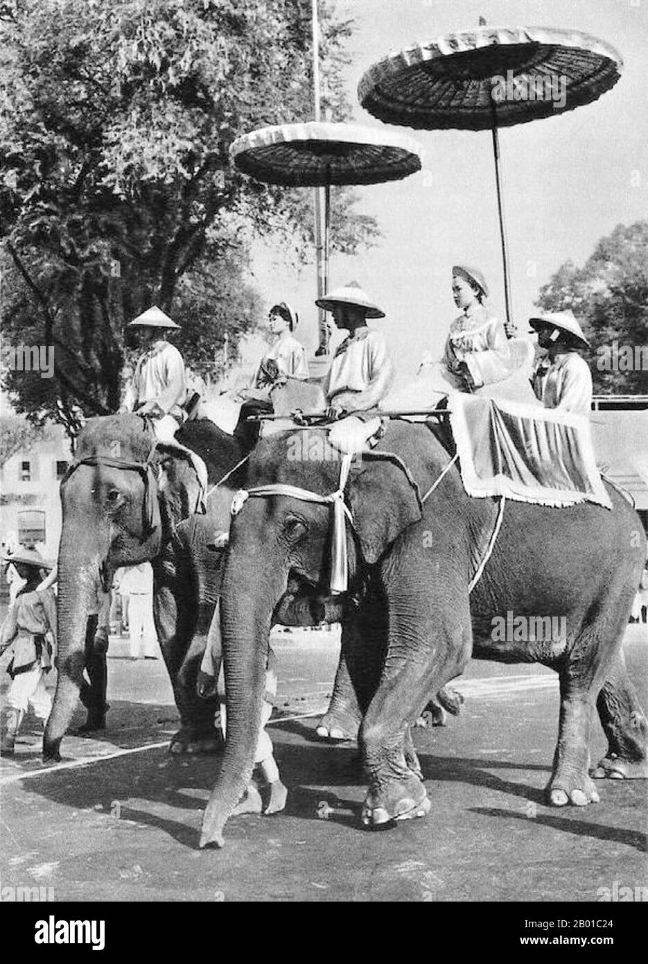 Two Vietnamese women on elephant back represent the celebrated Trung Sisters (Hai Ba Trung) in the annual Hai Ba Trung Parade, Saigon, 26 April 1957.  The Trưng Sisters (c. 12 - AD 43), known in Vietnamese as Hai Bà Trưng (literally 'the two Trưng Ladies'), and individually as Trưng Trắc and Trưng Nhị, were two first century Vietnamese women leaders who successfully rebelled against Chinese Han-Dynasty rule for three years, and are regarded as national heroines of Vietnam.  The sisters were born in Northern Vietnam, the dates of their birth are unknown, but Trưng Trắc was older than Trưng Nhị. Stock Photo