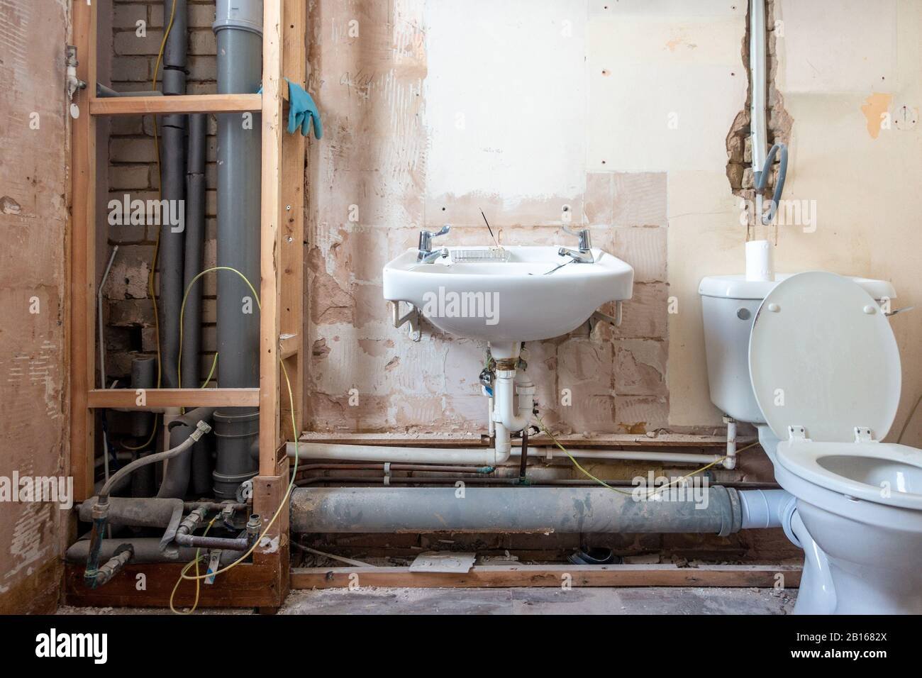 a-bathroom-stripped-bare-as-it-is-being-refurbished-and-modernised-pipes-plumbing-and-electrics-are-exposed-2B1682X.jpg