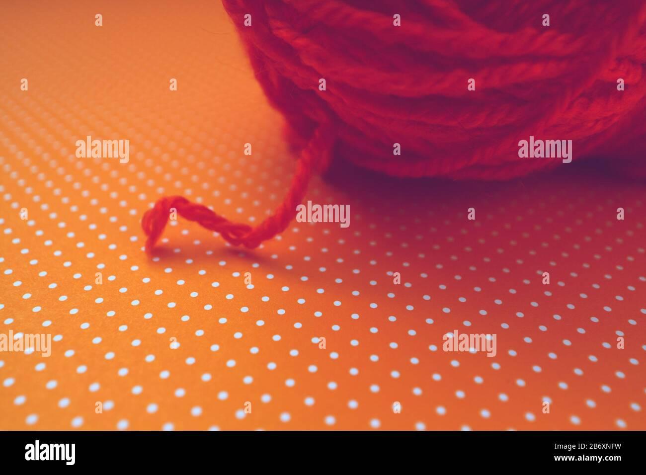 orange-yarn-ball-on-an-orange-dotted-bac