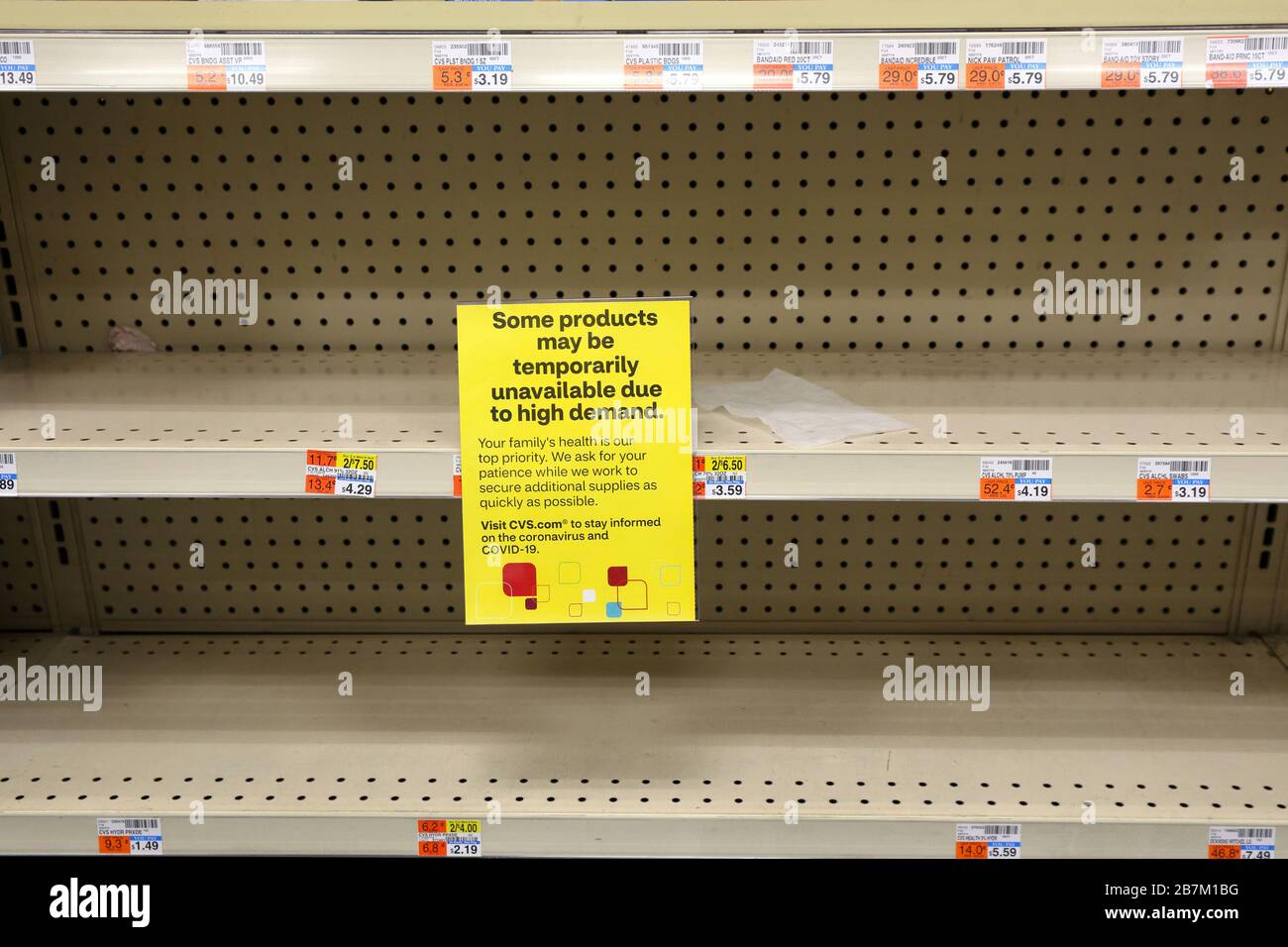 a-sign-warning-of-product-unavailability-sits-on-a-shelf-emptied-of-isopropyl-alcohol-and-bandages-at-a-nyc-chain-drug-store-march-16-2020-2B7M1BG.jpg