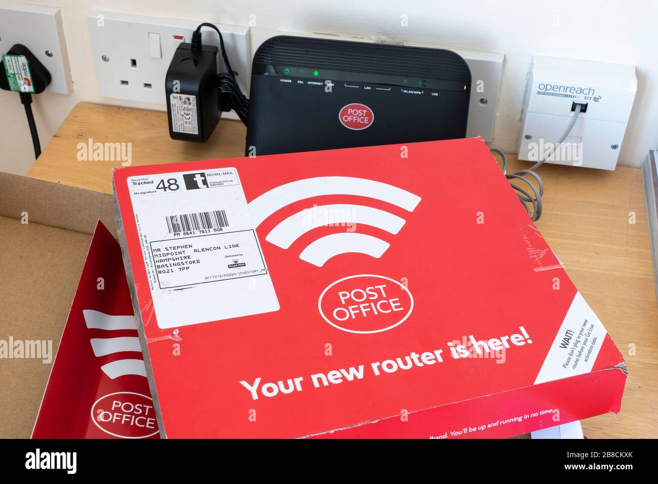 A broadband internet router connected to a wall socket sent by the Post Office - an internet provider -  to a home user in the UK Stock Photo