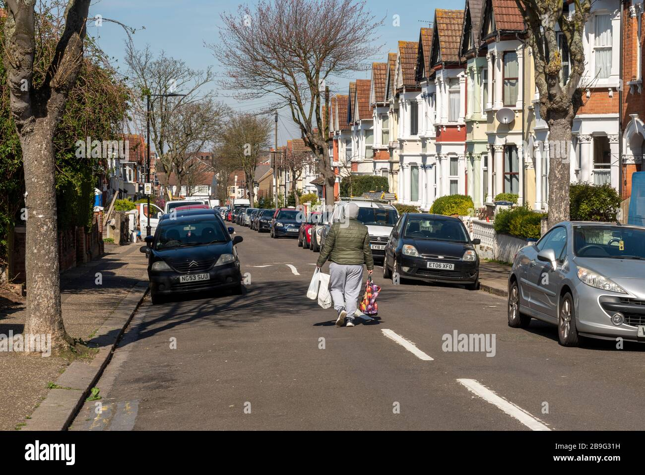 westcliff-on-sea-essex-uk-24th-march-2020-on-the-first-day-of-lockdown-in-the-uk-a-shopper-is-walking-home-in-the-middle-of-the-road-to-make-sure-of-avoiding-contact-with-other-people-during-the-covid-19-coronavirus-pandemic-outbreak-social-distancing-2B9G31H.jpg