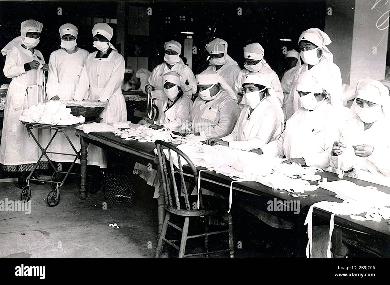 """Boston Red Cross volunteers assemble gauze influenza masks for use at hard-hit Camp Devens, Massachusetts. 1918-1919. An epidemic of """"Spanish Flu"""" spread around the world. At least 20 million died, although some estimates put the final toll at 50 million. Stock Photo"""