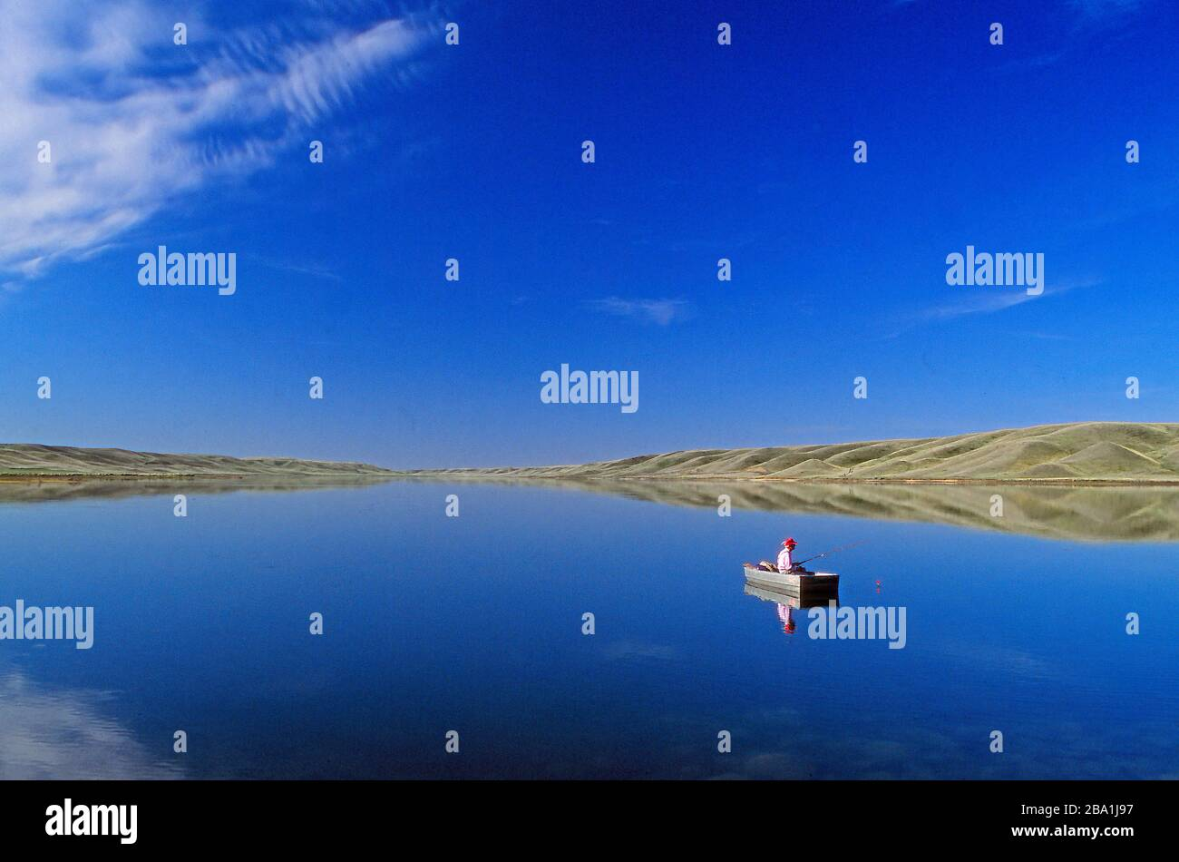 a-man-fishing-in-a-boat-on-the-tranquil-water-of-mcgregor-lake-alberta-canada-2BA1J97.jpg