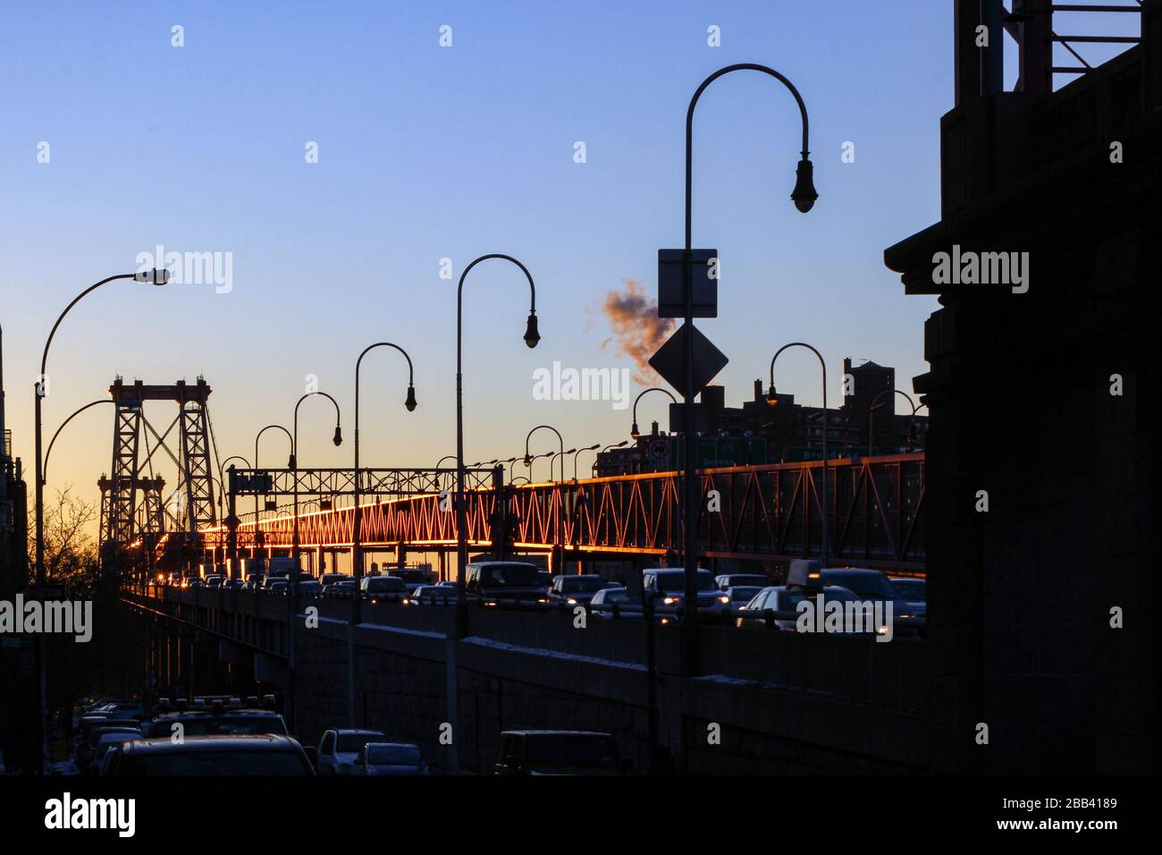 Cars on Lower East Side end of Williamsburg Bridge in the early morning rising sun in New York City, United States of America Stock Photo