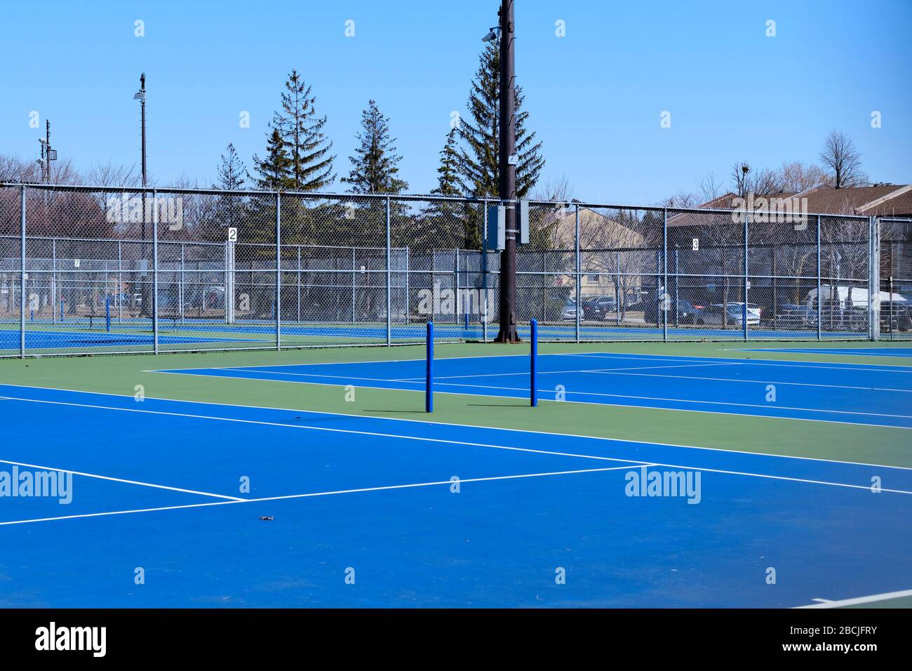 empty-tennis-court-on-sunny-spring-day-closed-due-to-covid19-epidemic-in-montreal-canada-2BCJFRY.jpg