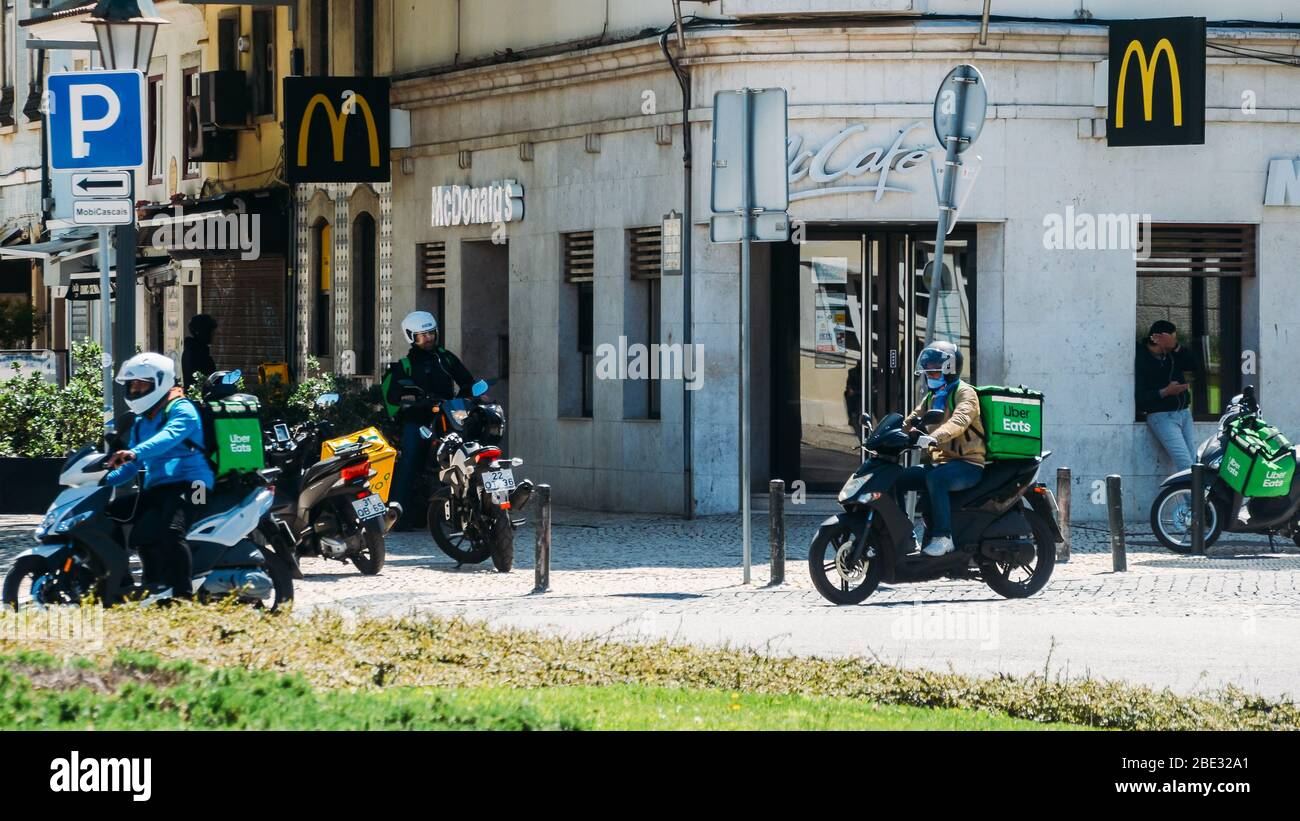 cascais-portugal-april-11-2020-glovo-and-ubereats-delivery-couriers-on-motorbike-in-front-of-a-mcdonalds-restaurant-during-the-coronavirus-covid-2BE32A1.jpg