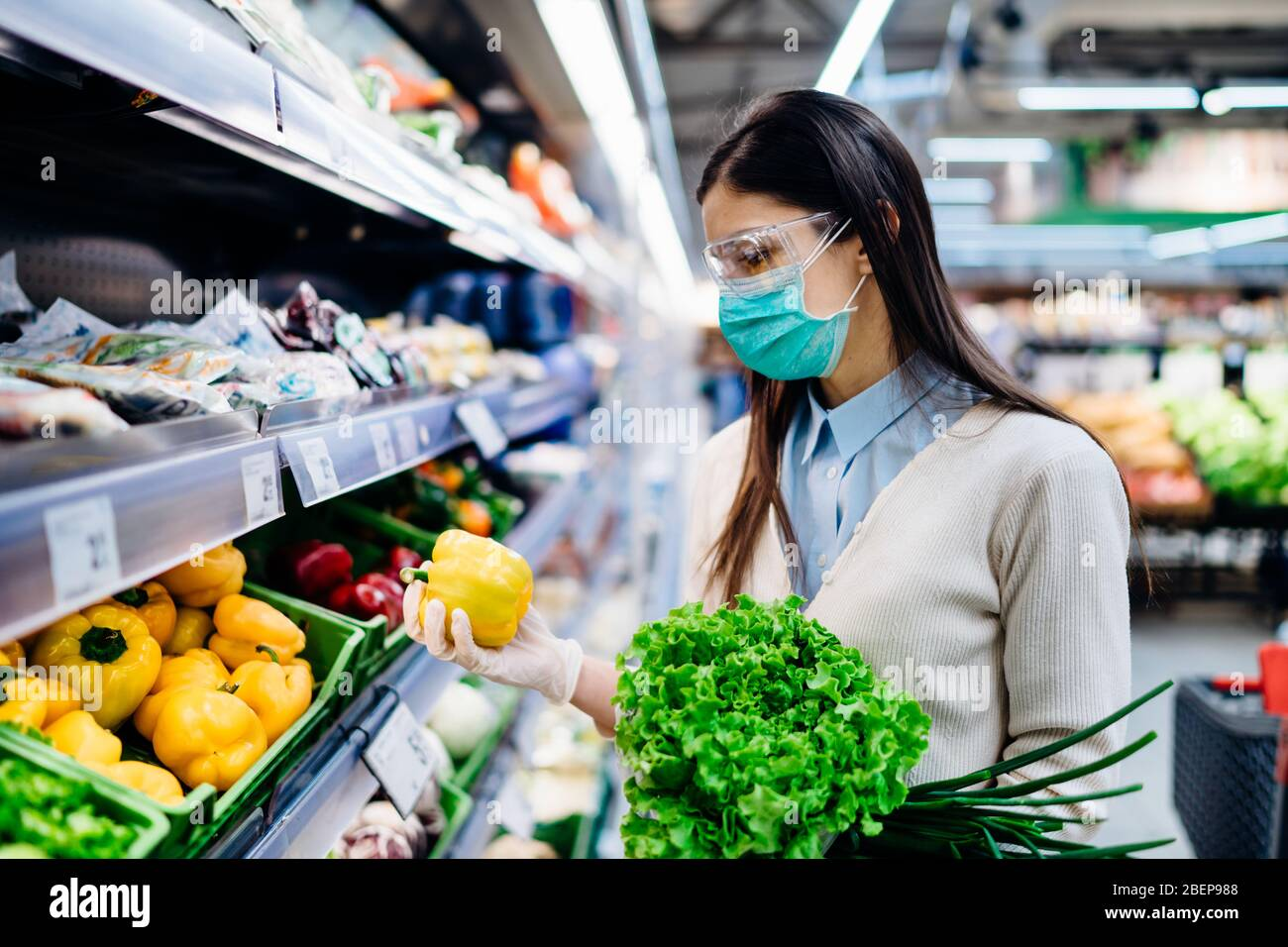 Woman with hygienic mask buying in supermarket grocery store for fresh greens,shopping during the pandemic.Natural source of vitamins and minerals.Pla Stock Photo