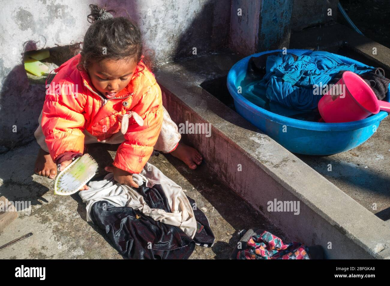 young-girl-child-working-and-washing-clo