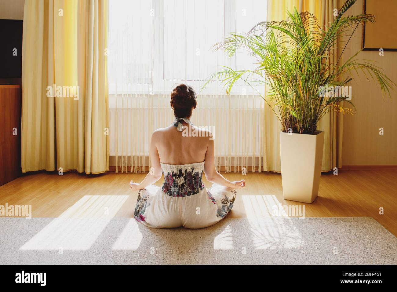 Back view of woman meditating on floor at home. Stock Photo