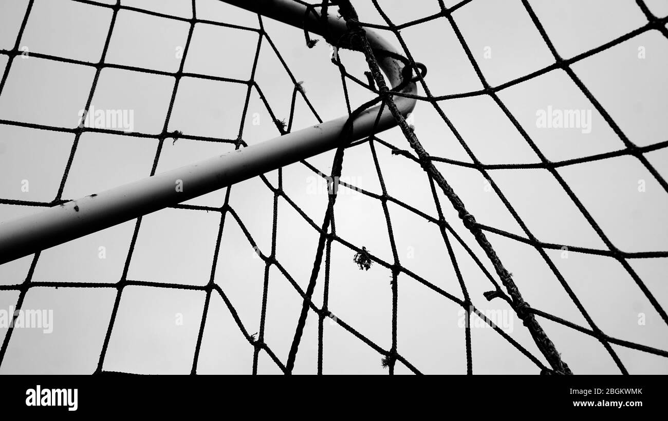 Black and white close up of a soccer net or soccer goal, twine mesh pattern, on a curved pole or bar, with a hole in the net. Stock Photo