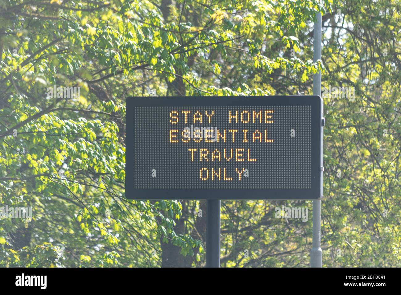 Traffic matrix sign beside A128 in Essex advising people to stay home, essential travel only, during COVID-19 Coronavirus pandemic lockdown period Stock Photo