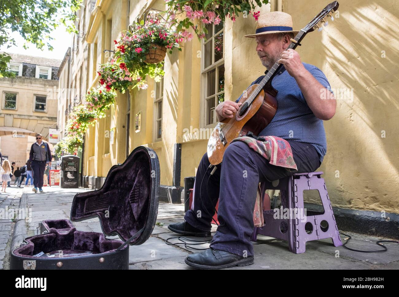 Busker playing Spanish classical guitar on street pavement, Bath, Somerset, England, GB, UK Stock Photo