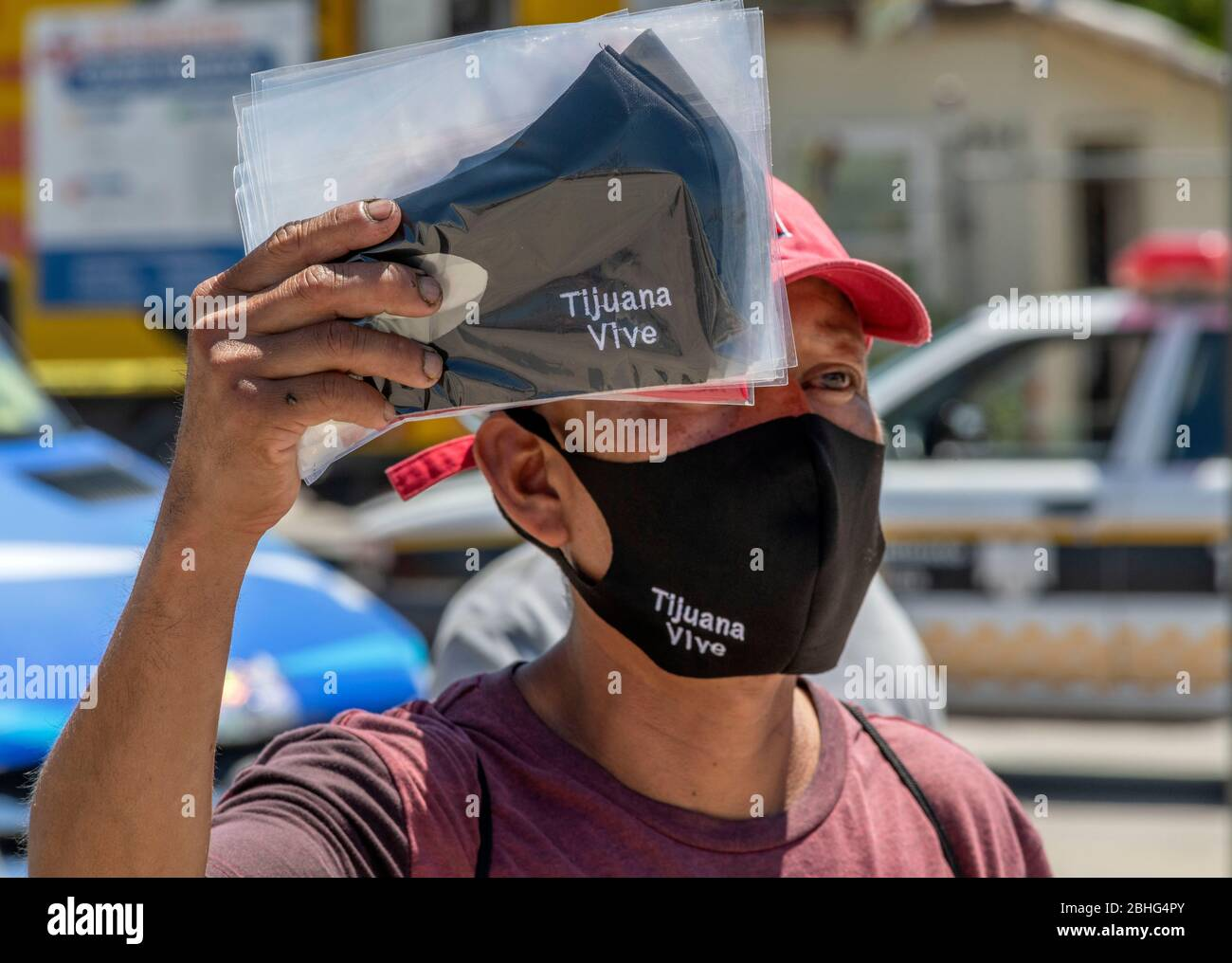Tijuana, Baja California, Mexico. 25th Apr, 2020. A man in Tijuana, Mexico, sells face masks near the San Ysidro US/Mexico border crossing. Tijuana is experiencing a very large number of coronavirus cases that are straining local hospitals' ability to care for patients. Credit: David Barak/ZUMA Wire/Alamy Live News Stock Photo