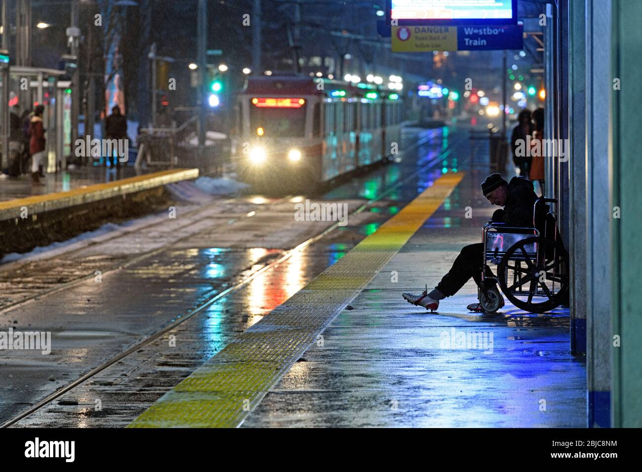 a-homeless-man-in-a-wheelchair-on-a-train-station-platform-during-a-rainy-night-calgary-alberta-canada-2BJC8NM.jpg